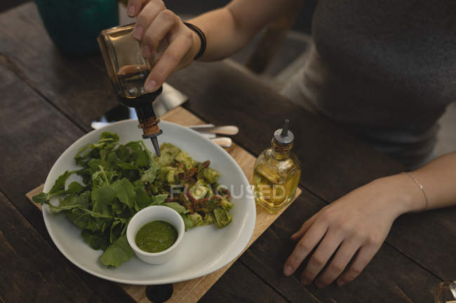 Young woman pouring soya sauce on salad at the coffee shop — Stock Photo