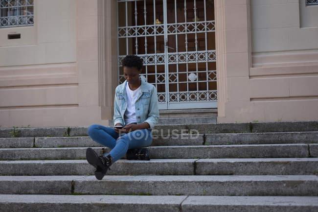 Женщина, использующая мобильный телефон на ступенях в городе — стоковое фото