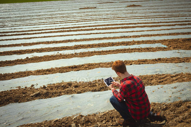Mann mit digitalem Tablet im Feld — Stockfoto