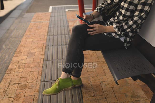 Низкая часть молодой женщины с помощью мобильного телефона, сидя на скамейке на тротуар — стоковое фото