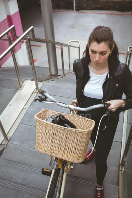 Belle femme avec vélo montant les escaliers — Photo de stock