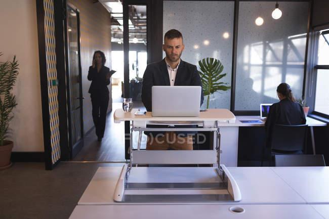 Uomo d'affari in piedi e utilizzando il computer portatile in ufficio — Foto stock