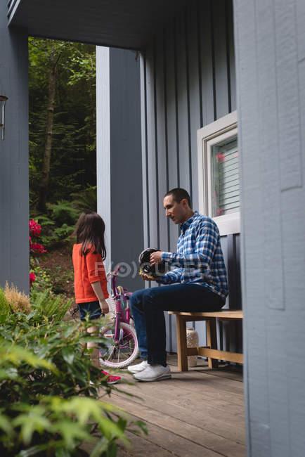 Отец, помогает его дочь поставить на велосипедный шлем на крыльце — стоковое фото