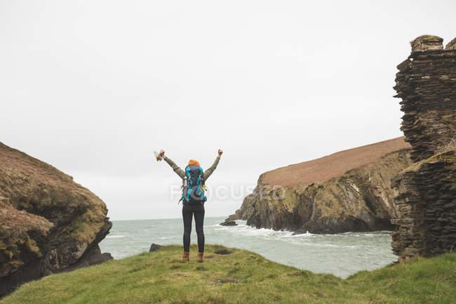 Vista trasera del excursionista femenino con los brazos extendidos de pie en la costa del mar - foto de stock