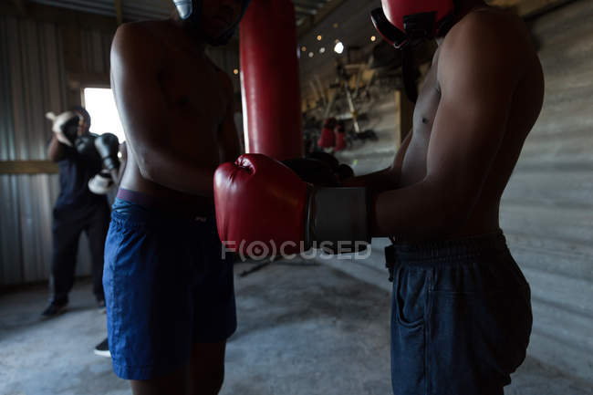 Trainer assisting young male boxer at fitness studio — Stock Photo