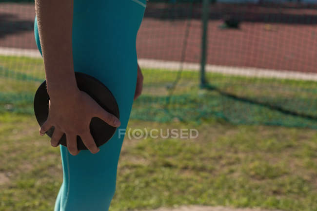 Mid section of female athlete practicing discus throw — Stock Photo