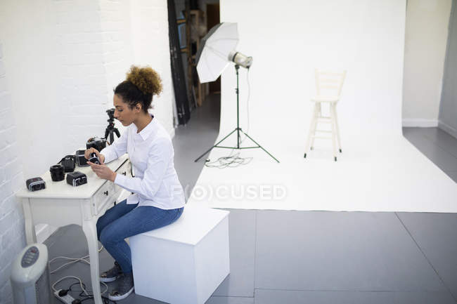 Fotografo femminile rimuovere bobina dalla fotocamera digitale in studio fotografico — Foto stock