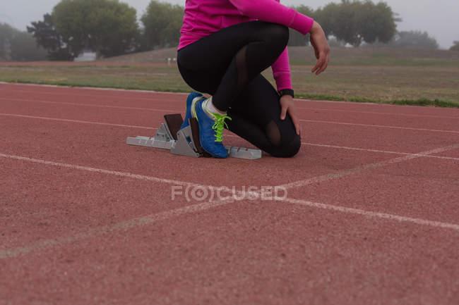 Низкая часть женского спортивная(ый) готовы к гонке на беговой дорожки — стоковое фото