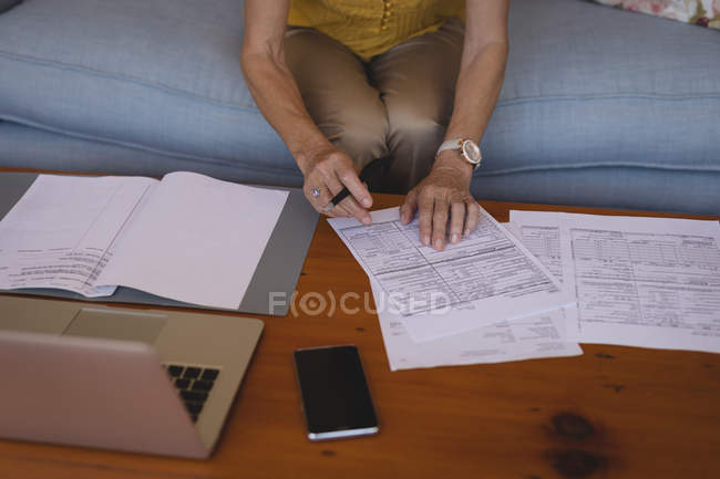 Mid section of senior woman checking bills at home — Stock Photo