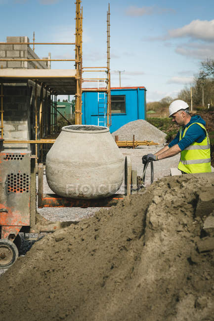 Engineer mixing cement in concrete mixer at construction site — Stock Photo