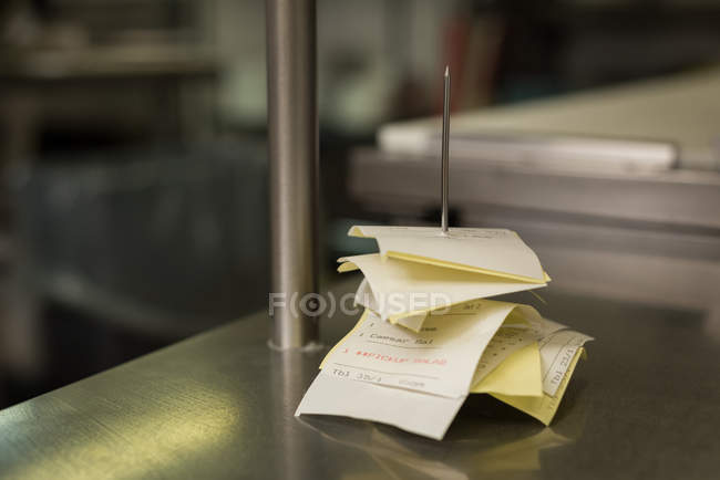 Close-up of bill on bill pin stand in kitchen — Stock Photo