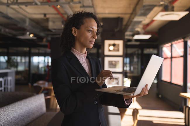 Donna d'affari in piedi e utilizzando il computer portatile in ufficio — Foto stock
