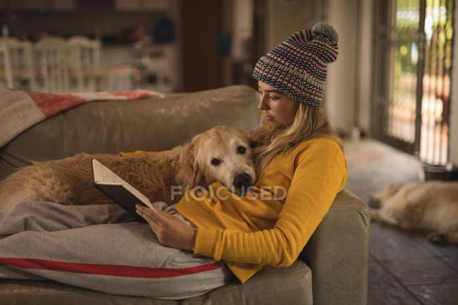 Mädchen mit Hund liest zu Hause im Wohnzimmer ein Buch — Stockfoto