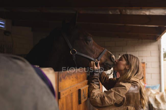 Teenager-Mädchen streichelt ein Pferd auf der Ranch — Stockfoto
