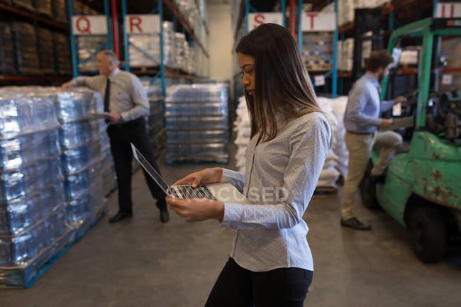 Женщина-супервайзер с ноутбуком на складе — стоковое фото