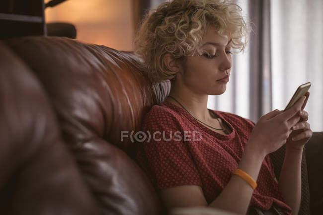 Jovem usando telefone celular na sala de estar em casa — Fotografia de Stock