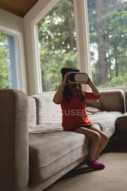 Дівчина за допомогою віртуальної реальності гарнітуру у вітальні на дому — стокове фото