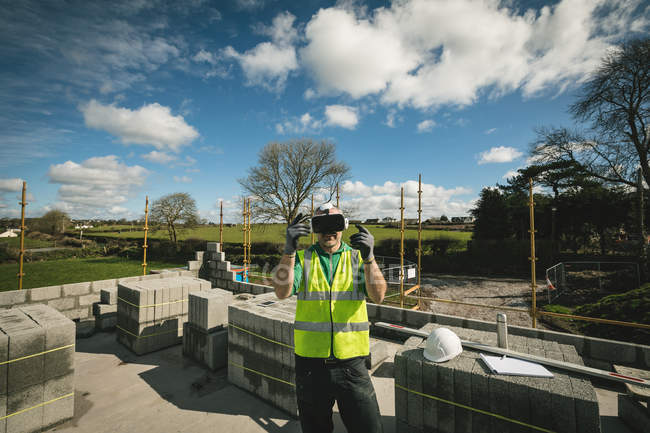Engineer experiencing VR headset at the construction site on a sunny day — Stock Photo