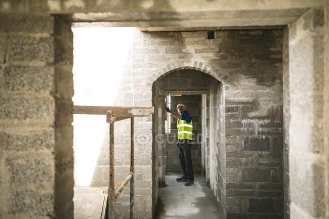 Инженер, делает проверку уровня в дверях на строительной площадке — стоковое фото