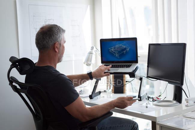 Homme préparant conception architecturale sur ordinateur portable et ordinateur à la maison — Photo de stock
