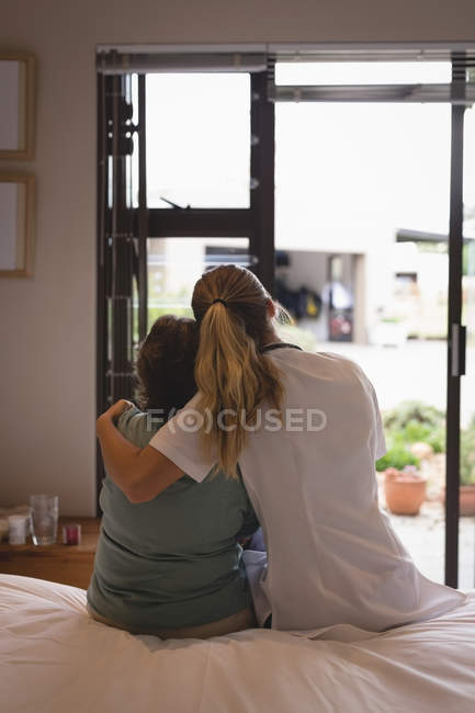 Rear view of physiotherapist embracing senior woman at home — Stock Photo