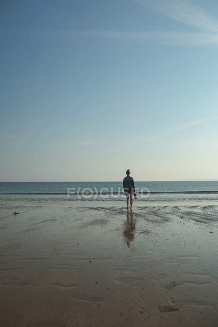 Rear view of woman standing on the sea beach on a sunny day — Stock Photo