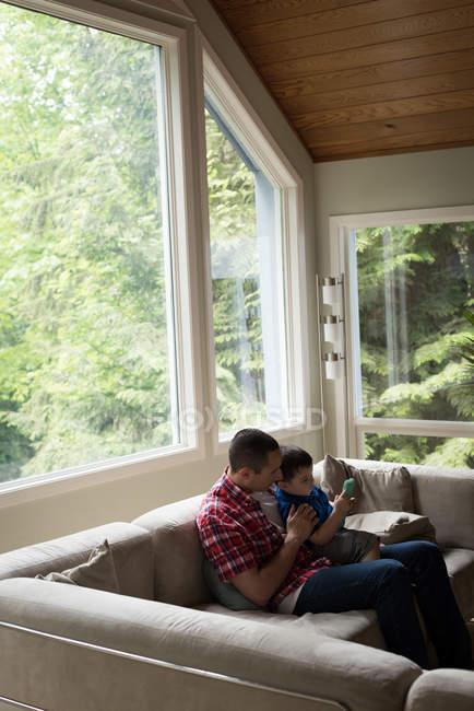 Батько і син, використовуючи цифровий планшетний у вітальні на дому — стокове фото