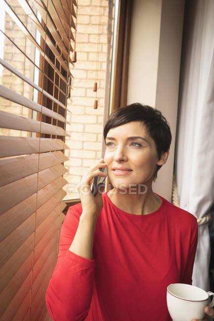 Женщина, имея кофе во время разговора на мобильный телефон дома — стоковое фото