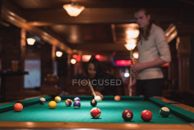 Couple playing snookers in night club — Stock Photo