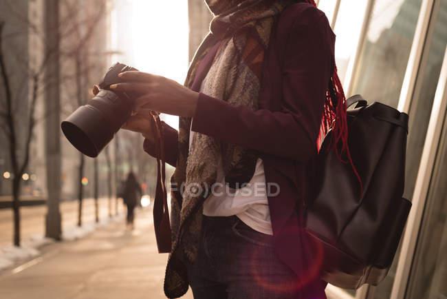 Розділ середині жінка з цифрової камери в міста — стокове фото