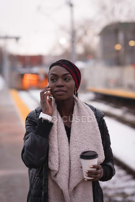 Молодая женщина разговаривает по мобильному телефону на вокзале — стоковое фото