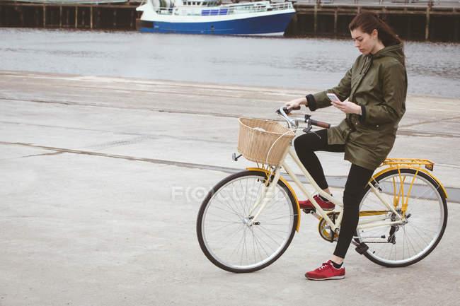 Bella donna in bicicletta utilizzando il telefono cellulare al porto — Foto stock
