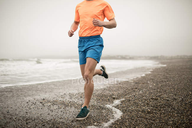 Low section of man jogging on shore at beach — Stock Photo
