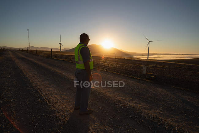 Rear view of engineer standing at a wind farm — Stock Photo