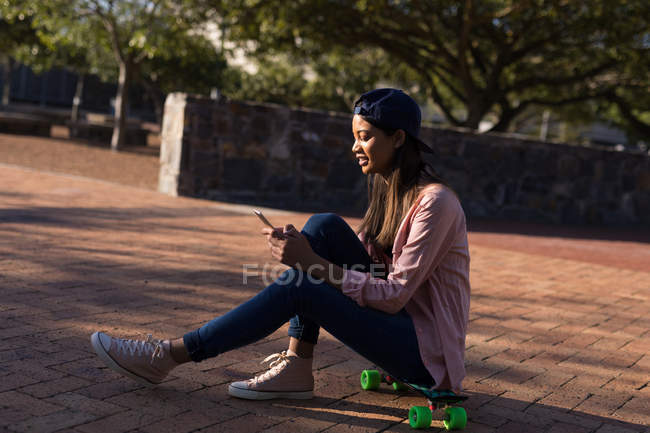 Young woman sitting on the skateboard using mobile phone — Stock Photo