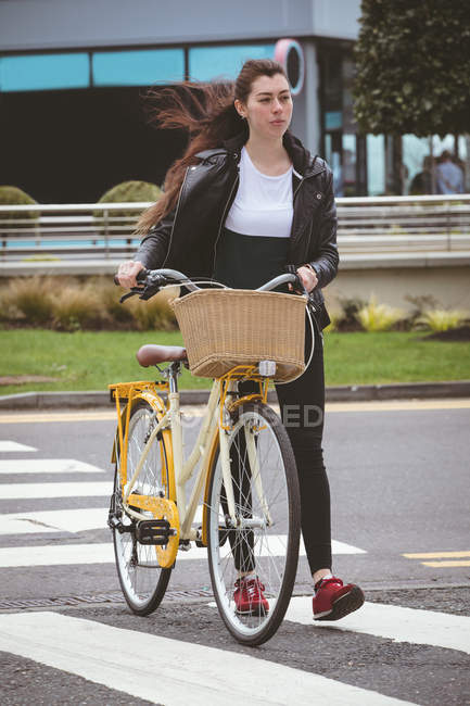 Beautiful woman with bicycle crossing road — Stock Photo