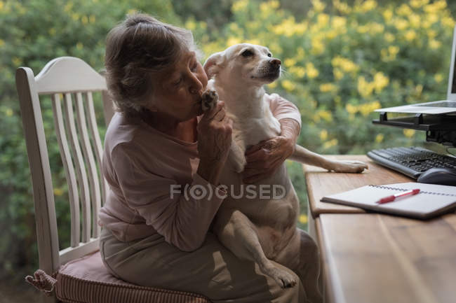 Senior woman kissing her dog while working at work table — Stock Photo
