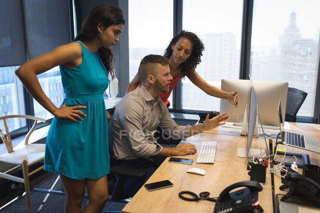 Business executives discussing over desktop at office — Stock Photo