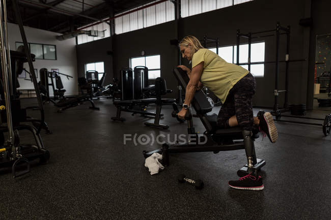 Disabled woman exercising on machine in the gym — Stock Photo