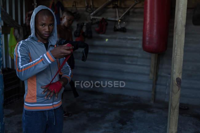 Boxeur masculin attacher enveloppement main sur la main à la salle de fitness — Photo de stock