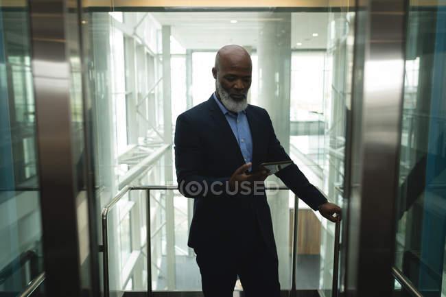 Homme d'affaires à l'aide de tablette dans l'ascenseur au bureau — Photo de stock
