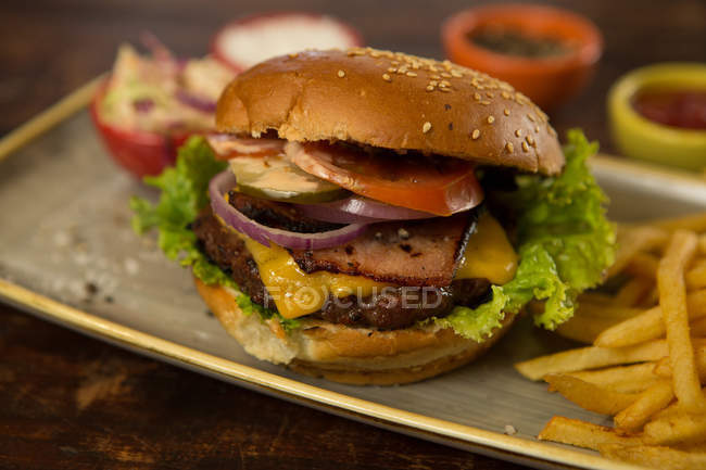 Meat burger with french fries served on wooden table — Stock Photo