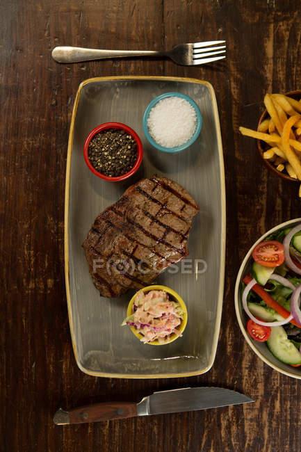 Hambúrguer de carne com batatas fritas servido em mesa de madeira — Fotografia de Stock