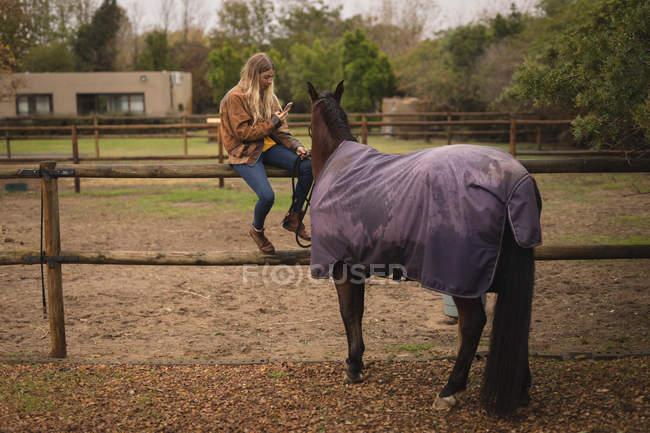 Mädchen mit Pferd benutzt Handy auf der Ranch — Stockfoto