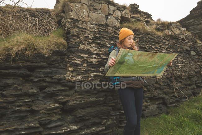 Hermosa excursionista femenina apoyada en la roca y leyendo un mapa - foto de stock