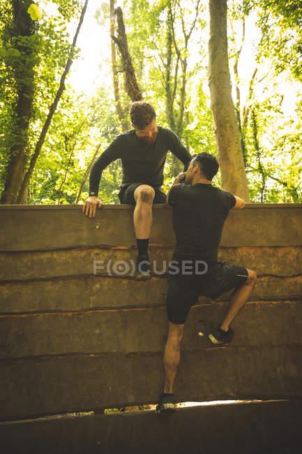 Подходящие мужчины тренируются на полосе препятствий в учебном лагере — стоковое фото