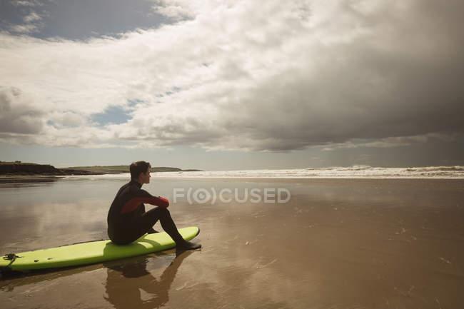 Вид сбоку серфера, сидящего на доске для серфинга на пляже и смотрящего на море — стоковое фото