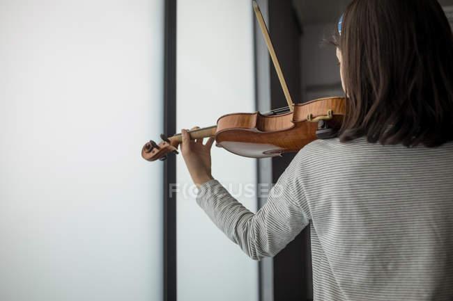 Rückansicht einer Schülerin, die in der Musikschule Geige spielt — Stockfoto