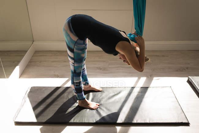 Женщина занимается спортом с гамаком для перевязок в фитнес-студии — стоковое фото