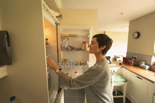 Женщина ищет еду в холодильнике дома — стоковое фото